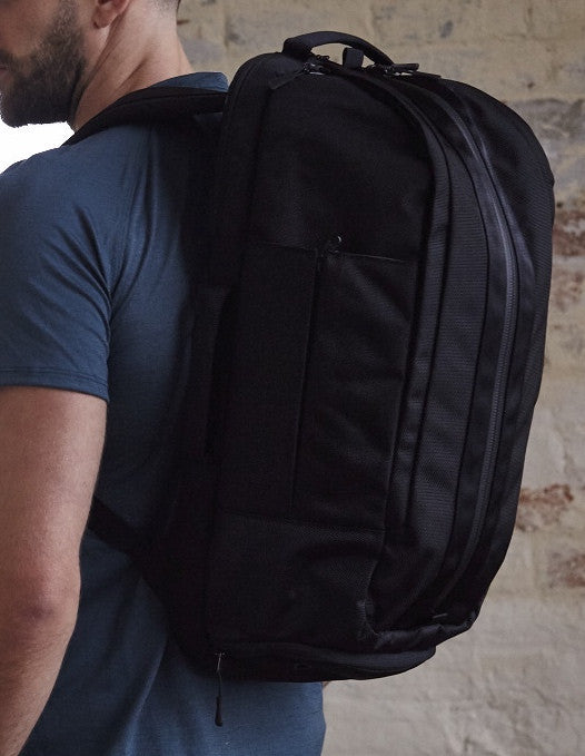Detail of side of black Aer Duffel Pack rucksack worn by model