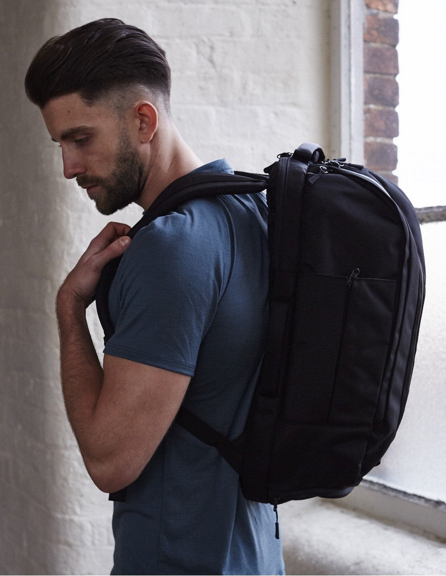 Model wearing black Aer Duffel Pack rucksack and cobalt Olivers Apparel Convoy T-Shirt