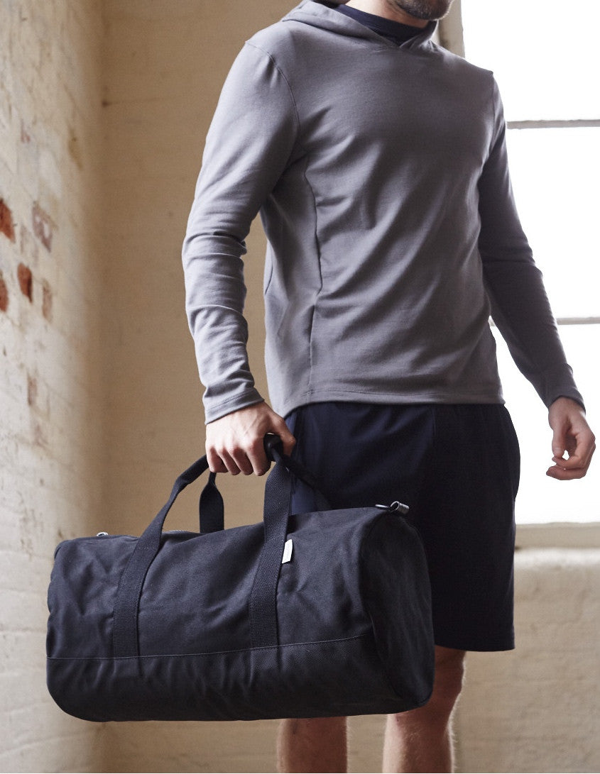 Side of Black Work Hard, Play Hard canvas duffel bag by Owen & Fred held by man