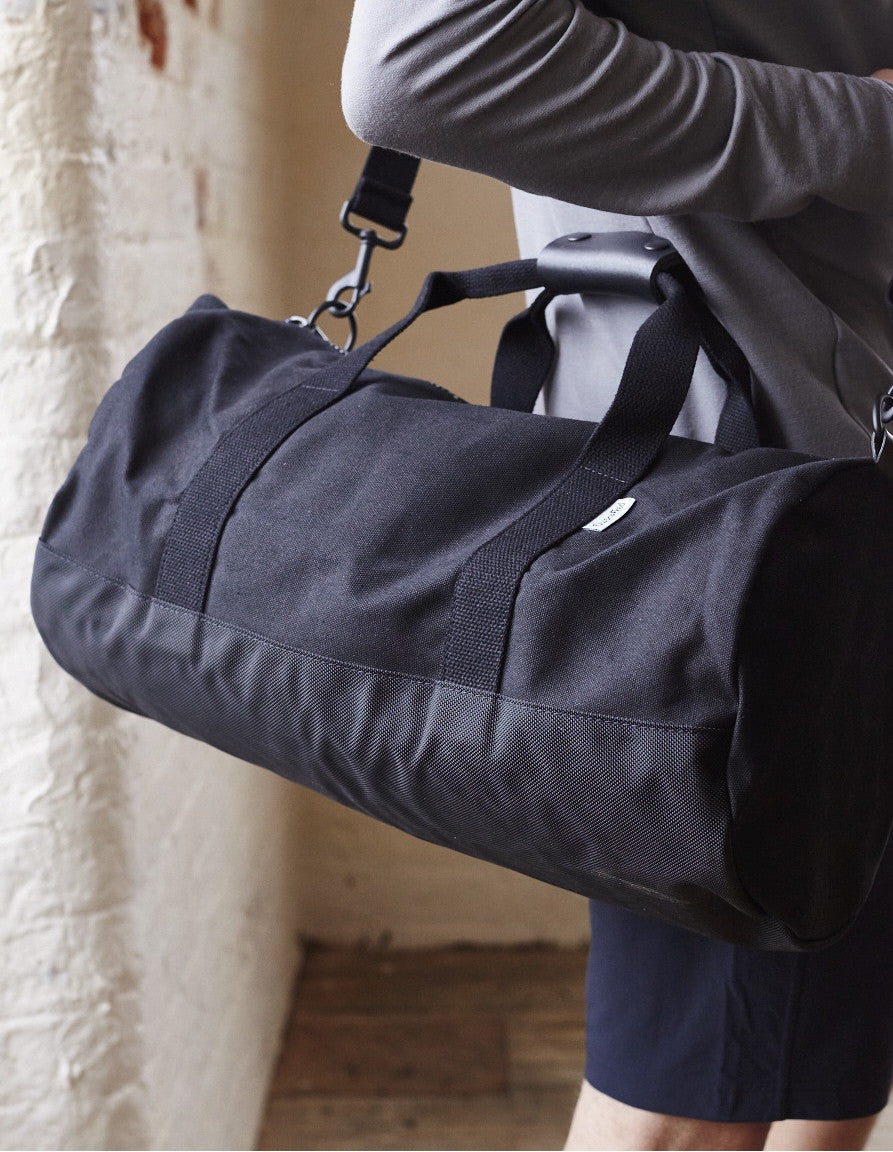 Side of Black Work Hard, Play Hard canvas duffel bag by Owen & Fred over man's shoulder