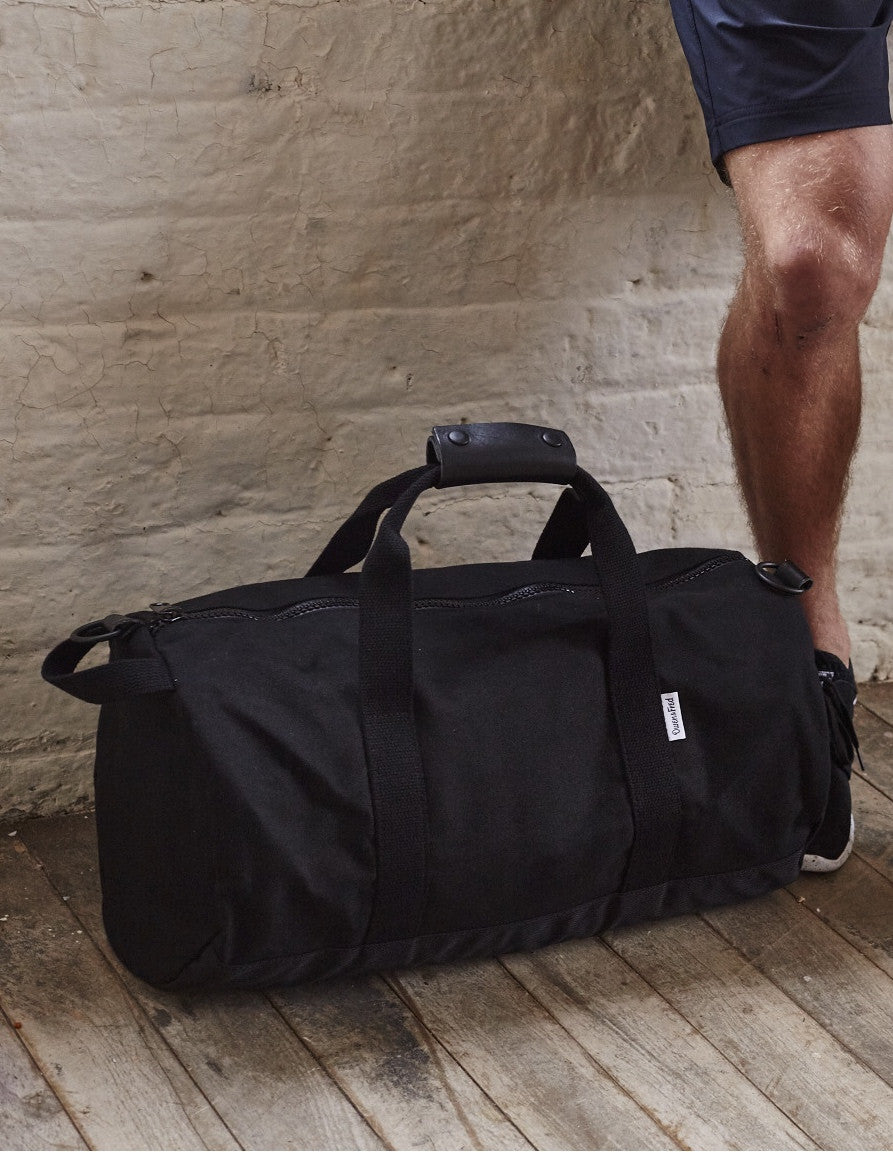 Side of Black Work Hard, Play Hard canvas duffel bag by Owen & Fred with man's legs