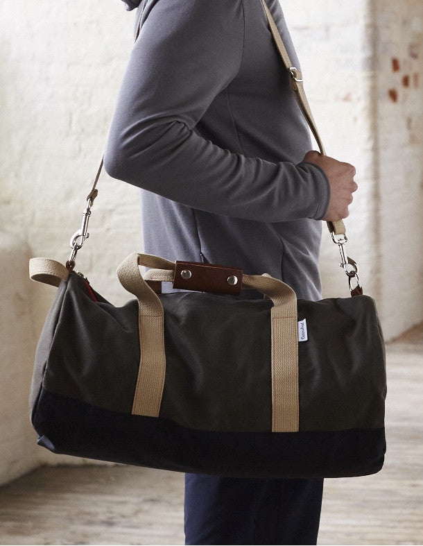 Side of man holding Army Green Work Hard, Play Hard duffel bag by Owen & Fred