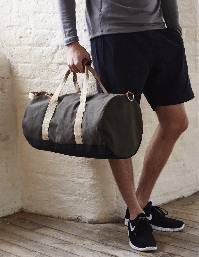 Man holding Army Green Work Hard, Play Hard duffel bag by Owen & Fred
