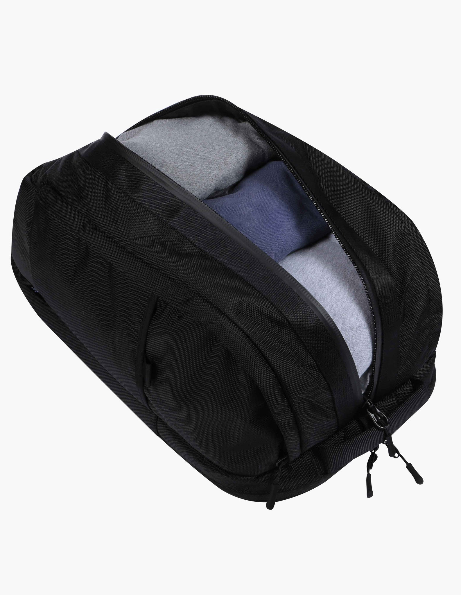 Full view of of black Aer Duffel Pack rucksack with zip open main pocket showing sports clothes