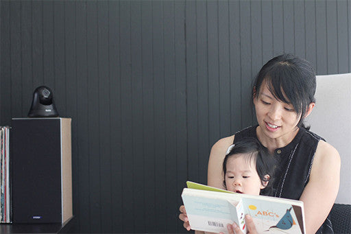 A mother reading a book to her baby with V15 in the background