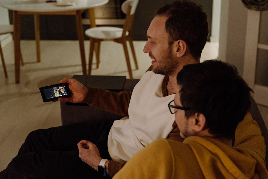 Two sitting men looking at a smartphone