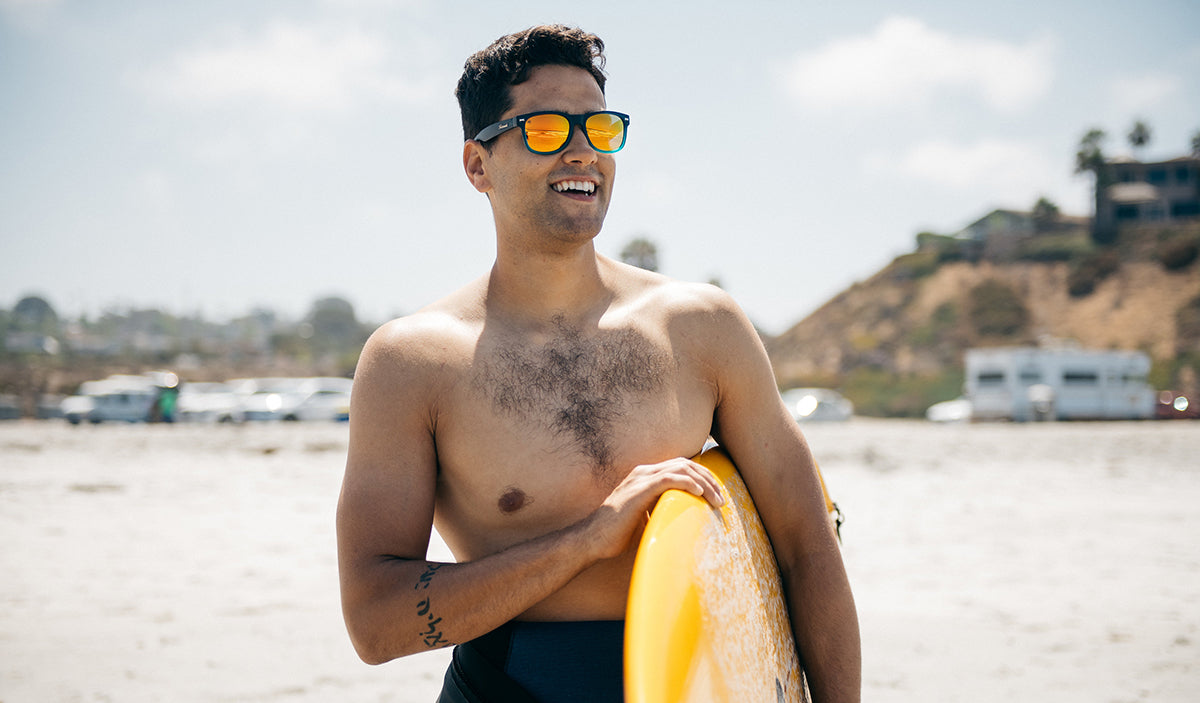 Man holding surfboard and wearing polarized Knockarounds