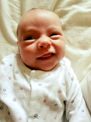 A baby girl smiles because she is well-fed and happy after her parents discovered Minbie and avoided nipple confusion