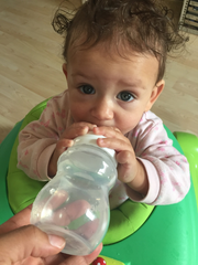 A baby girl drinks from a Minbie bottle