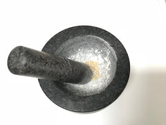 Grinding Frankincense resin in a pestle and mortar