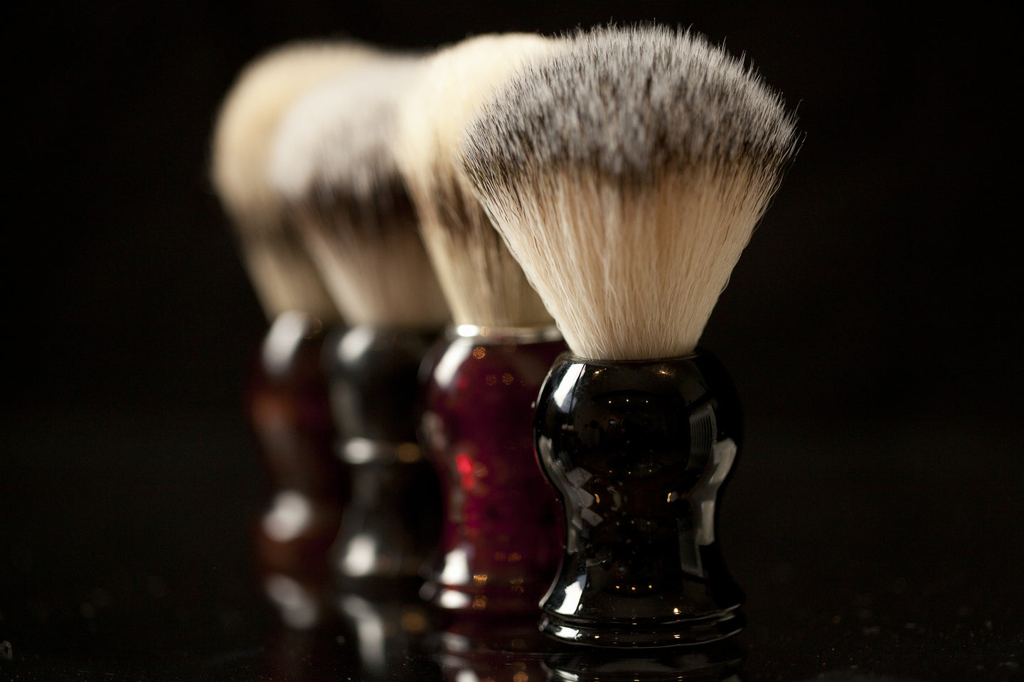 row of shaving brushes black background