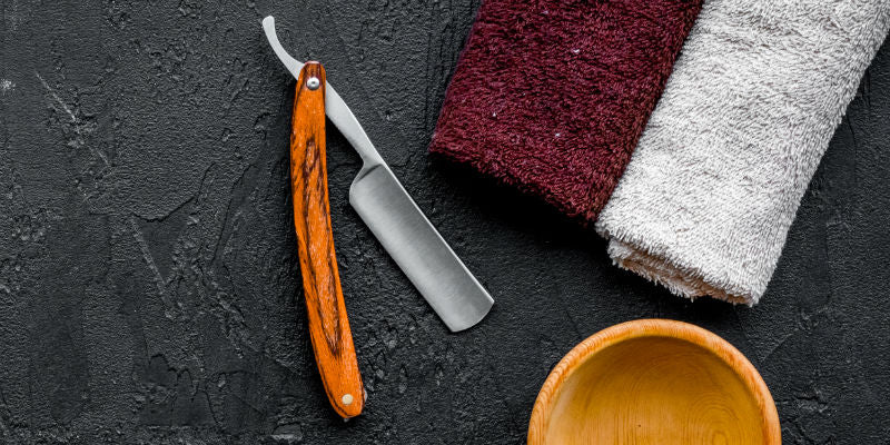 top-down view of cut-throat razor, towel, and bowl, on slate surface