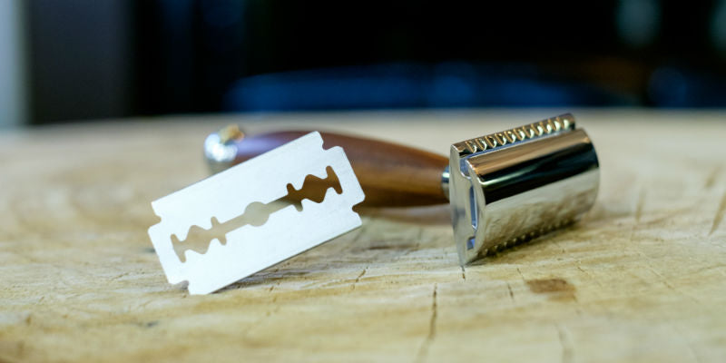 traditional safety razor and DE blade on wooden surface