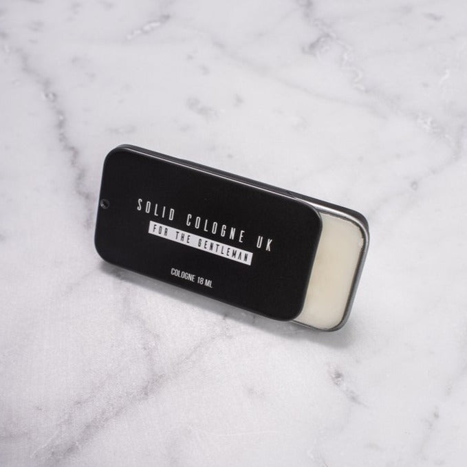 Solid cologne 'Malcolm' scent black tin on marble background