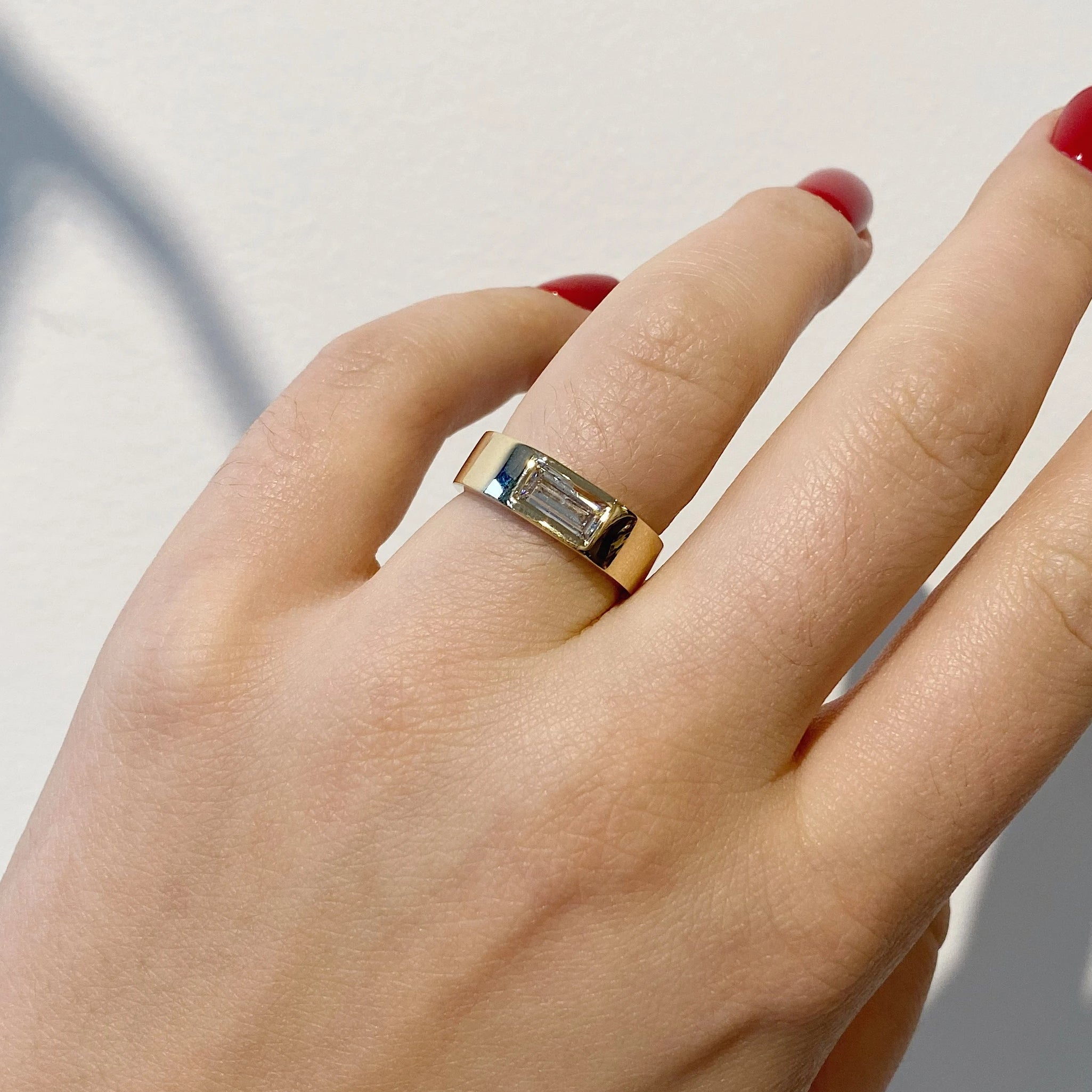custom wide band ring with burnish set baguette