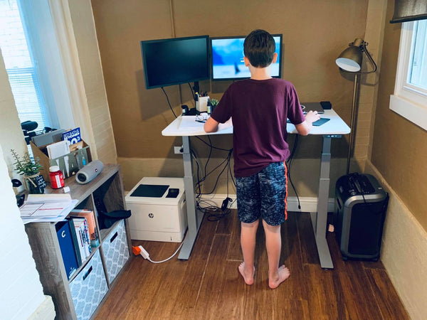 Child standing at standing desk