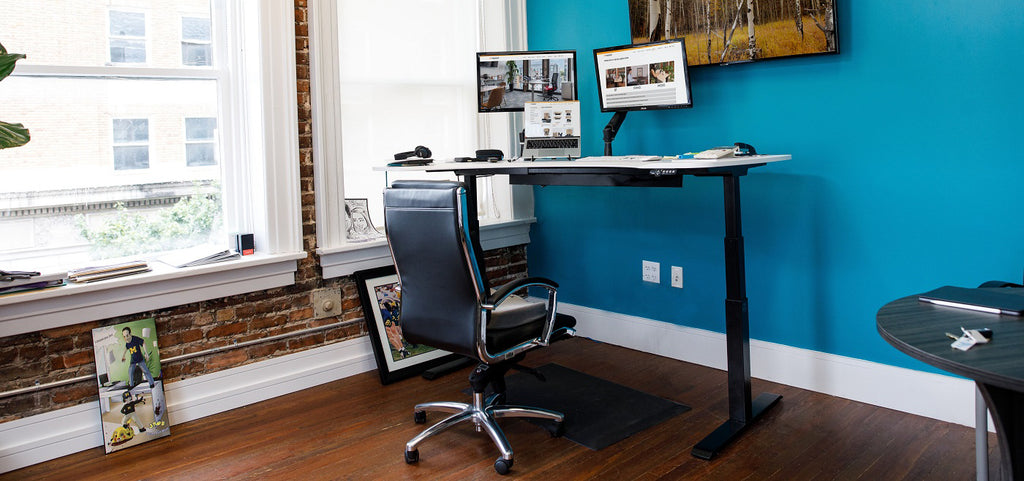 Standing Desk shown up position blue wall
