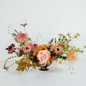 Floral compote arrangement with peach and pink flowers