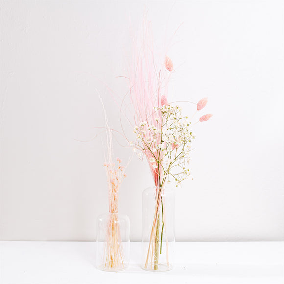 Pink and peach dried flowers in two glass bud vases