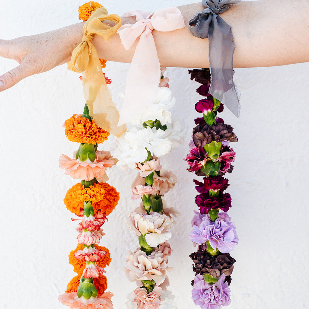 Three multicolored flower necklaces with carnations and marigold flowers