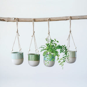 Four ceramic hanging planters in shades of blue and green with fern plant