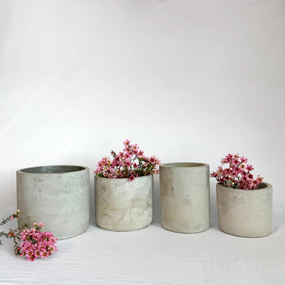Four cement vases with pink flowers
