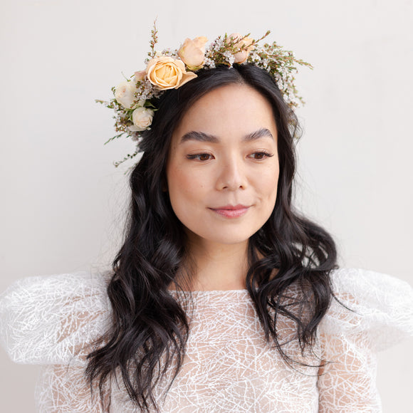 Woman with dark hair wearing Grace flower crown from Native Poppy