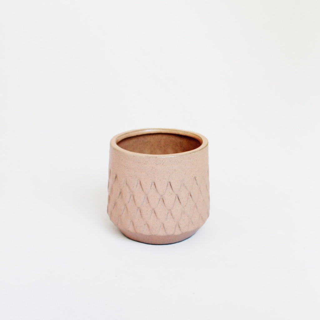 Pale pink vase with scallop design reminiscent of fish scales.