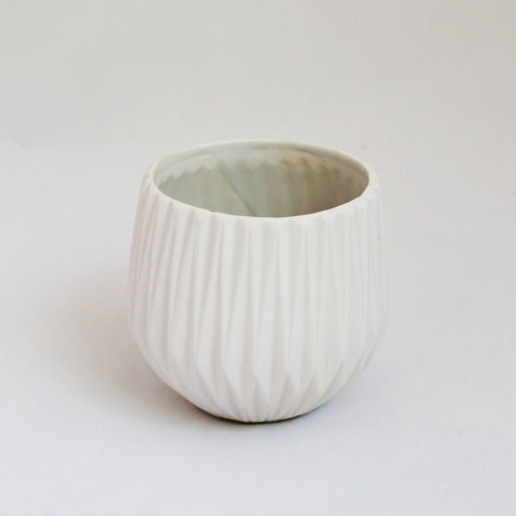 geometric white ceramic pot with angular, symmetrical design all around.