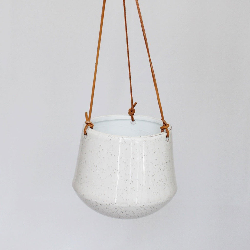 Large, rounded bottom hanging pot from leather that tapers towards the top.
