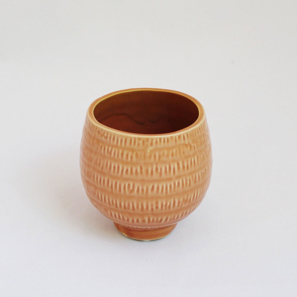 Little coral colored vase with tiny hash mark designs all over it.