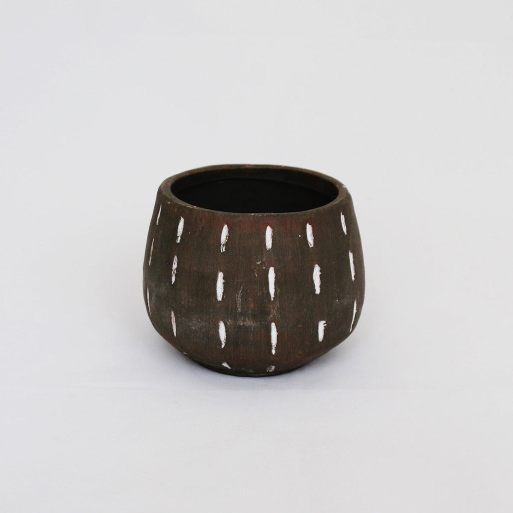 Gray ceramic pot with white vertical scratch designs.