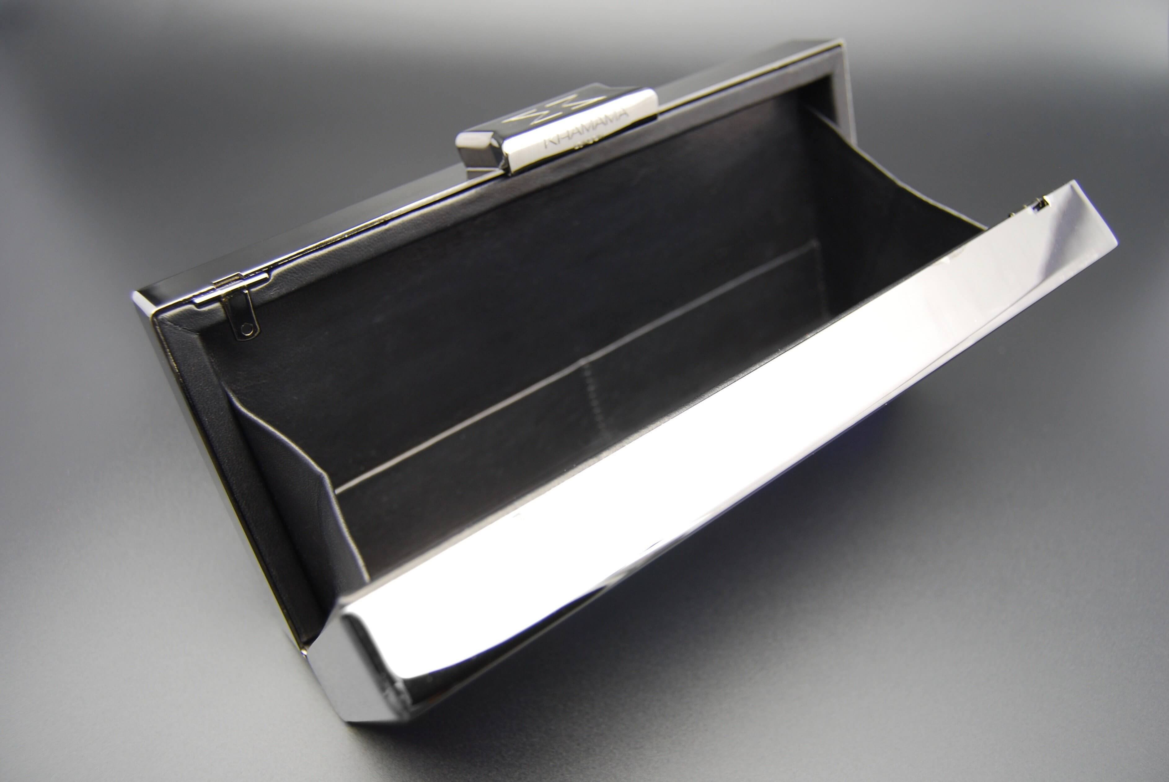 Clutch made from brass with smooth leather interior