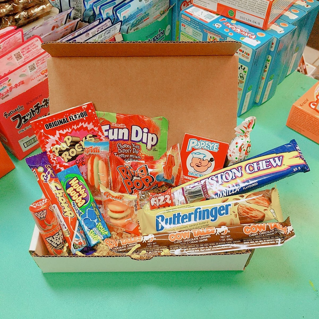 Photo of a box with a variety of chocolate bars and candies displayed open and overflowing. Charleston Chew, Butterfinger, Fun Dip, Pop Rocks, Hubba Bubba, Cow Tales and much more!
