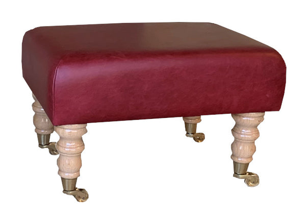 Aged Claret Leather Footstool with Natural Caster Legs