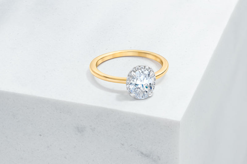 Essex VOW by Ring Concierge oval halo engagement ring with plain band in yellow gold. 33281380679768