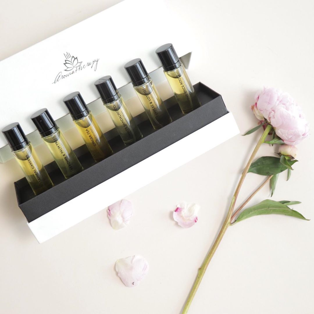 Lily Aromatherapy's clean perfume set, the Scent Journey Set is placed next to a pink peony flower with a few petals
