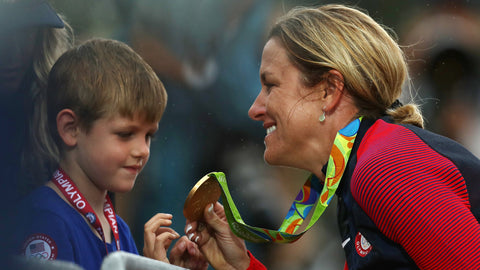 kristin armstrong with gold medal and child