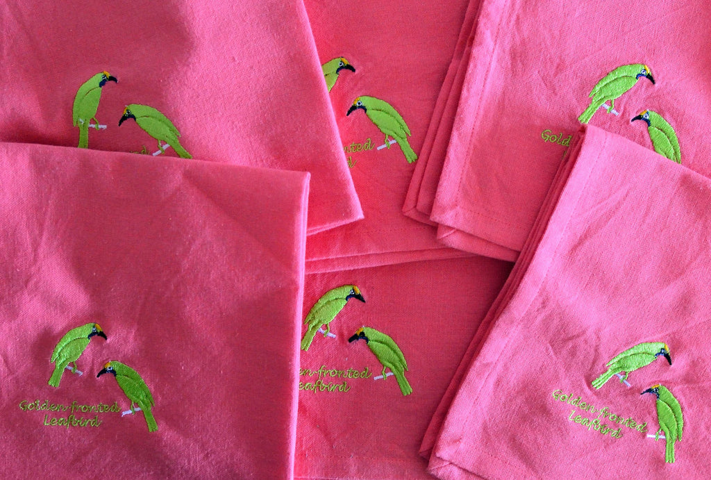 EMBROIDERED NAPKINS: GOLDEN FRONTED LEAFBIRD ON A PEACH PINK COLOURED NAPKIN
