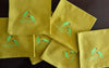 EMBROIDERED NAPKINS: GOLDEN FRONTED LEAFBIRD ON A MUSTARD YELLOW COLOURED NAPKIN