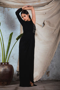 Black knit jersey one sided sleeve draped gown with corset embellishment and slit in the front