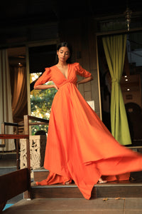 Orange dress with a plunging draped neckline and cut out back