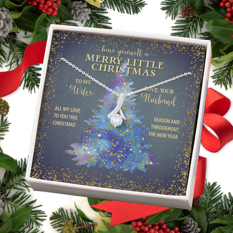 """Have Yourself a Merry little Christmas. To My Wife- All My Love to You this Christmas Season and Throughout the Year- Love, Your Husband""  Melt her heart with this ALLURING BEAUTY necklace gift! The petite ribbon shaped pendant is finished with 14K white gold over stainless steel, and is embellished with dainty clear crystals surrounded by a"