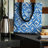 Image of Indigo tote bag with black handles. three sizes. Sturdy polyester comfortable beach or town. Tote on kitchen counter.