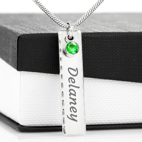 This simple yet elegant name plate pendant is the perfect way to show appreciation to your loved ones. Engrave a unique message or name onto the plate and select one of our shimmering birthstones to represent a member of your family, a close friend, or for yourself! This beautiful piece makes a truly one-of-a-kind gift for yourself or someone special. Polished Stainless Steel engraved with a name and dangling birthstone of choice.