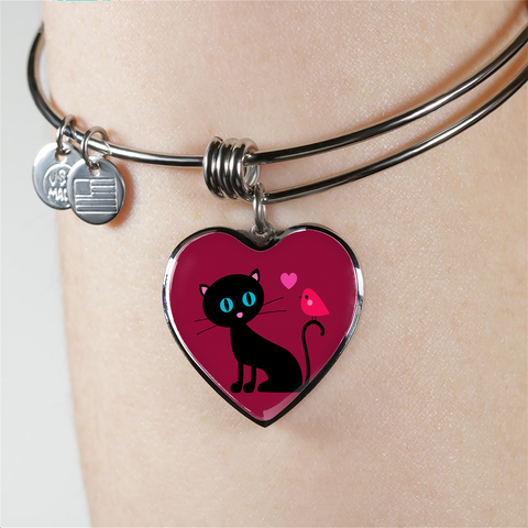surgical stainless steel bangle bracelet with heart shaped charm with patent pending poured glass dome, black cat with orange bird and pink heart, maroon background, made and shipped from USA personalized engraving on back ,  gift box comes free with product, free engraving, shown on woman's arm