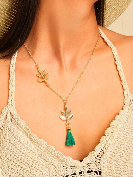 Necklace in gold colour with leaf details and emerald green tassel