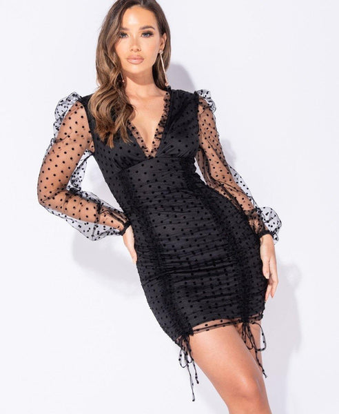 Long sleeve mini dress in black with sheer fabric detail on sleeves and layered over dress