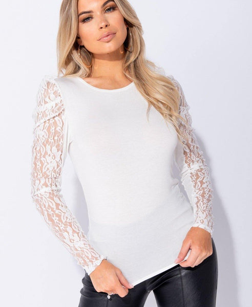 Ladies white, long sleeve top with sheer lace sleeves.
