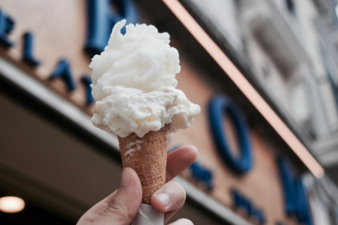 A person holding up a plain icecream cone in front of a store